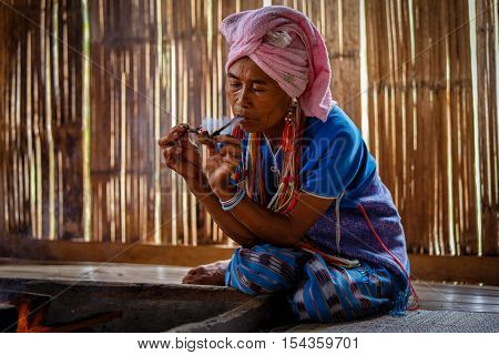 Female karen hill tribe is smoking tobacco pipe traditional in the cottage of northern Thailand at Mae Klang Luang Mae Chaem Chiang Mai Province