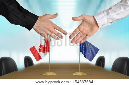 Canada and European Union diplomats shaking hands to agree deal