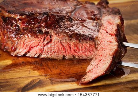 medium roast rib-eye steak on wooden background