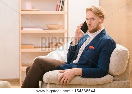 Hnadsome rich European businessman using mobile or smart phone for talking with foreing business partners concerning new conceptions, strategies.