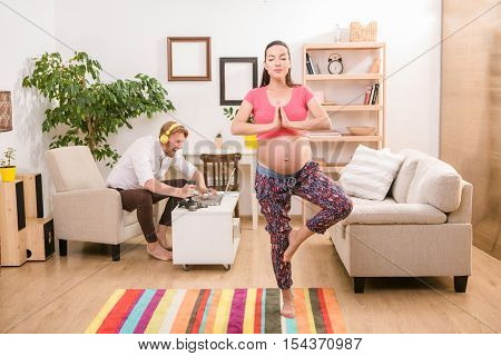 Health and pregnancy concept. Young pregnant woman training yoga at home. Brunette lady clasped her hands and concentrating on baby. Her husband using laptop computer for playing compuer games.