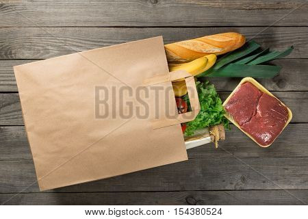 Different food in paper bag on wooden background. Grocery shopping concept top view