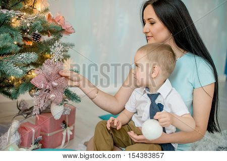 Beautiful mother and young son sitting on the farm near the Christmas tree of gifts. The concept of Christmas