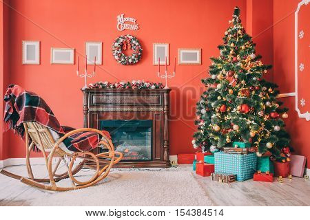 Beautiful New Year Room With Decorated Christmas Tree, Gifts, Wicker Rocking Chair And Fireplace. Th