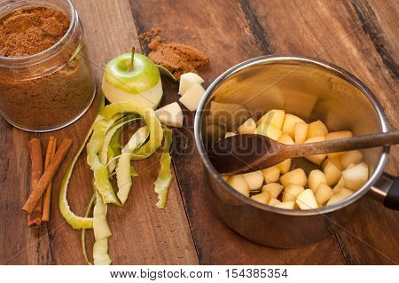 Preparing homemade apple and cinnamon sauce with fresh peeled and sliced green apples in a pot alongside stick cinnamon and ground spice on a wood table