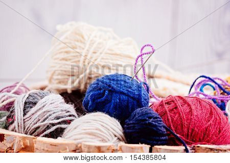 Colorful Wool Balls And Needles In Wooden Basket