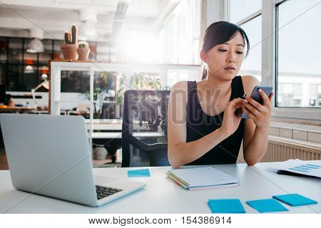 Portrait of young asian woman sitting at her desk with laptop and adhesive notes using mobile phone. Asian businesswoman working in modern office.