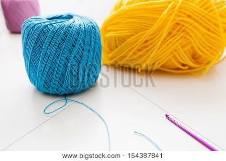 Bright colorful balls of yarn and crochet. Knitting equipment on white background, free space for text. Leisure, handiwork, hobby, handiwork concept