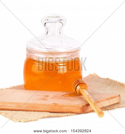 Fresh liquid honey in a glass jar and a wooden spoon isolated on white background