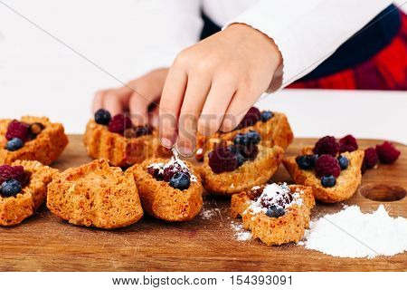 Child hand stuff cakes with fresh berries close-up. Little girl cooking sweets for family. Homemade bakery, children culinary, pastry making concept