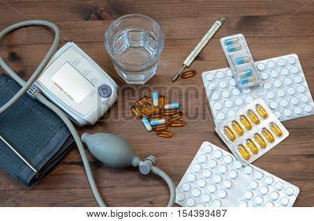 Water glass tonometer and medicaments on wooden background