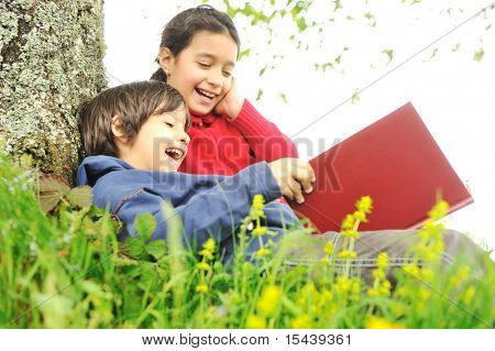 Happy children reading the book under the tree