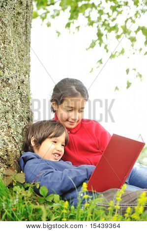 Crianças felizes, lendo o livro sob a árvore