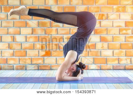 Asian trainee strong woman practicing difficult yoga raja kapotasana King pigeon pose in a concrete background