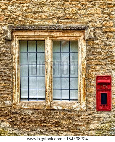 An old red postbox next to a house window in an English village.