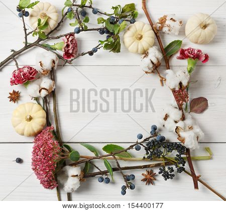 Autumn composition background. Frame made of dried fall flowers, pumpkins, branches and autumn leaves, also cotton, clove and sloe. Top view on white wood, flat lay, copy space in middle