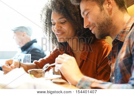 Couple in restaurant eating chocolate cake