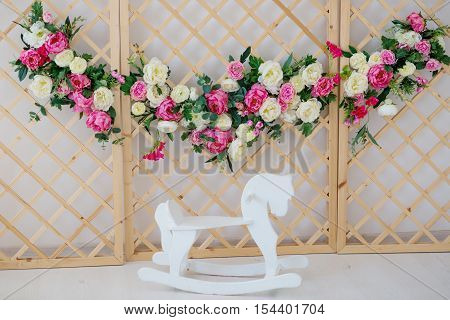 a flower wreath standing near the wooden horse rocker in the room