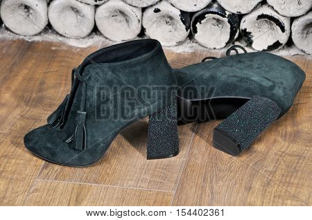 Pair of bright suede shoe with high heels. Sexy Women's boots handmade on a background of antique bottles. Dark green ankle boots.