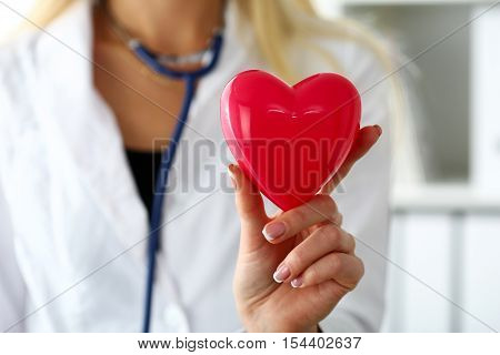 Female Medicine Doctor Wearing Hold In Hands Red Toy Heart