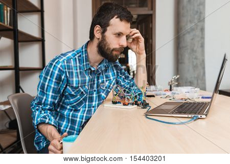 Bearded engineer waiting for program download, free space. Programmer sitting at workplace with cup of coffee and looking at laptop screen, testing new computer program