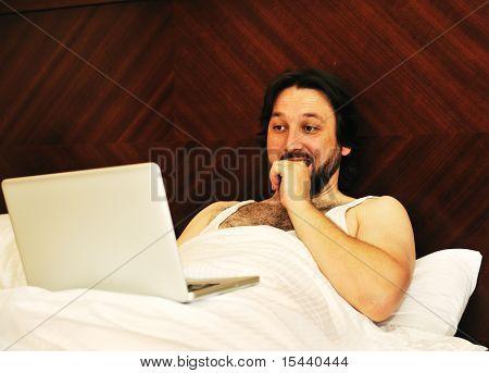 Man on laptop in bedroom looking at