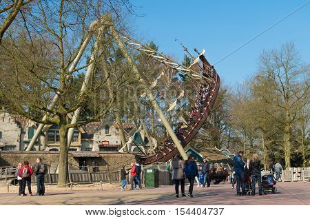 KAATSHEUVEL NETHERLANDS - MARCH 13 2016: Unknown people at a swinging ship in The Efteling the largest theme park in the Benelux
