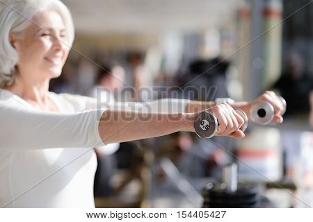 Exercise with smile. Joyful senior fit woman smiling during weight training while exercising in the gym.