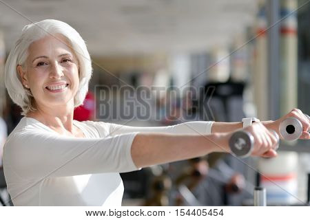 Happy training. Inspiring senior joyful woman smiling and staying fit by lifting weights in a gym.