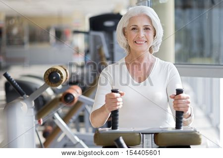 Cheerful workout. Attractive senior joyful woman smiling and staying fit by using equipment in a gym.