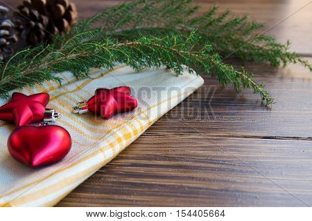 Christmas or New Year background. Natural fir tree brunch and cones with traditional decoration on wooden rustic table. Red glitter star and heart on vintage napkin. Winter holidays concept. Copy space