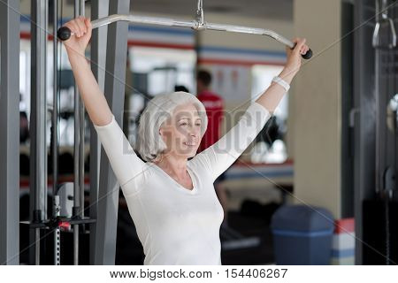 Inspiring fitness. Joyful athletic senior woman smiling and training back muscles by using sports equipment in the gym