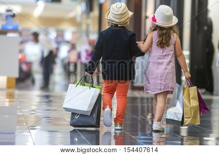 Kids shopping. cute little girl and boy on shopping. portrait of kids with shopping bags.
