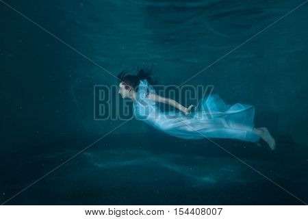 Woman at the bottom of the pool she under the water like a fairy tale.