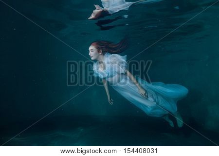 Fairy woman in a white dress under water it looks like a mermaid.