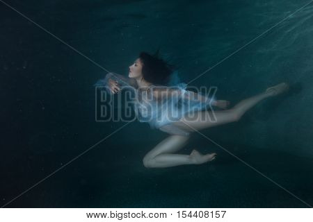 Woman under the water like a fairy tale she dances on the bottom.