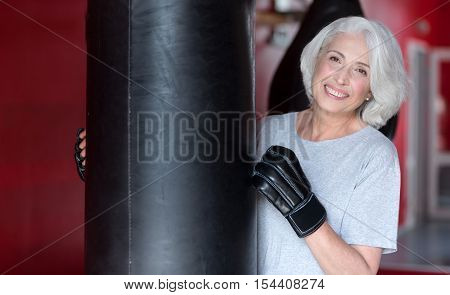 Glad beautiful senior woman smiling and touching punching bag while training in a gym and having boxing lesson.