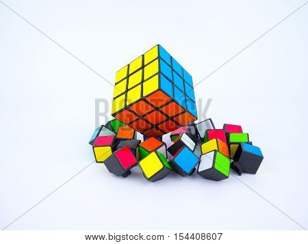 Bangkok Thailand - October 27th 2016: Colorful Rubik's cube and broken cube pieces on white background