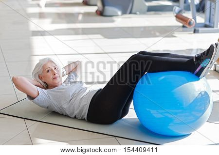 I will do it. Ambitious pretty senior woman laying on a floor and putting legs on a fit ball while doing sit ups.