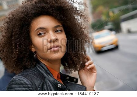 Ethnic girl waiting for taxi cab in New York city