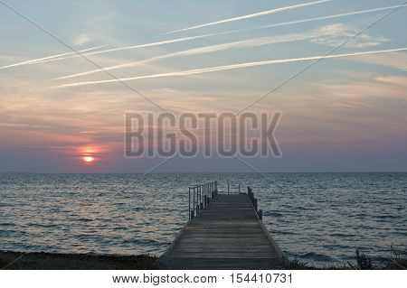Sunrise at a beach with a bathing jetty
