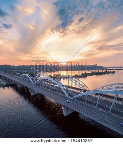 Automobile and railroad bridge in Kiev, the capital of Ukraine. Bridge at sunset across the Dnieper River. Kiev bridge against the backdrop of a beautiful sunset in Kiev. Bridge in evening sunshine.
