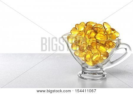 Glass sauce boat with fish oil capsules on light background
