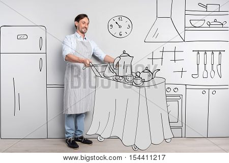 Delivering breakfast. Handsome optimistic good looking man standing in the kitchen and pushing the serving trolley while delivering breakfast
