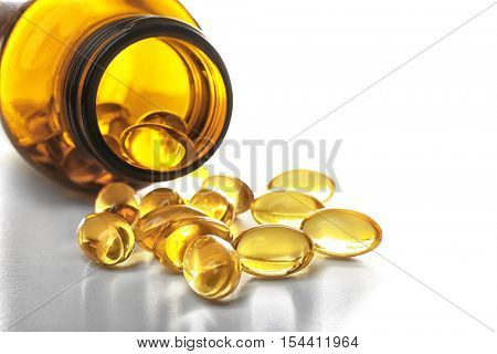 Glass bottle and capsules of fish oil on light background, close up view