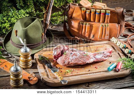 Preparing venison by a hunter on old wooden table