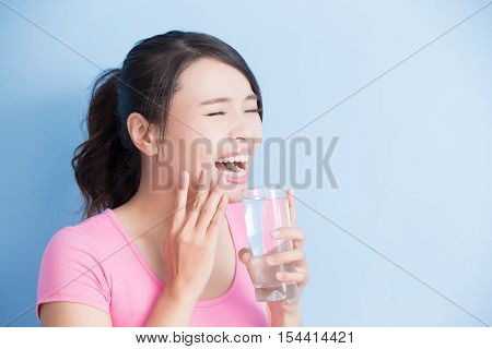 woman drink water with sensitive teeth isolated on bluebackground