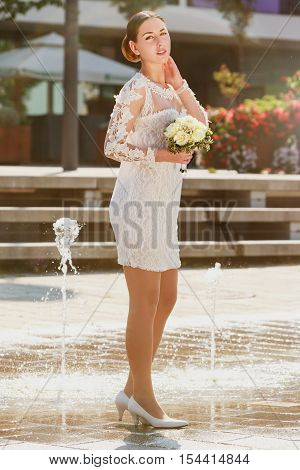 A beautiful bride stands in front of a fountain