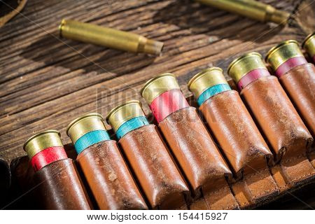 Closeup of belt with hunter bullets on old wooden table