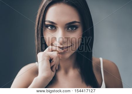 Feeling playful tonight. Attractive young woman holding hand on chin and looking flirty while sitting against grey wall